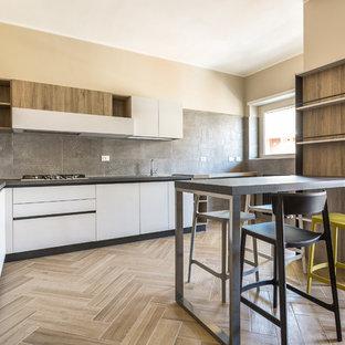 Esempio di una cucina a L design con ante lisce, ante bianche, paraspruzzi grigio, top grigio, penisola e pavimento beige