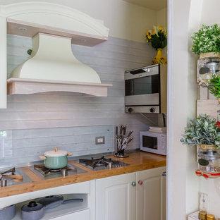 他の地域のシャビーシック調のおしゃれなキッチン (レイズドパネル扉のキャビネット、白いキャビネット、木材カウンター、ガラス板のキッチンパネル) の写真