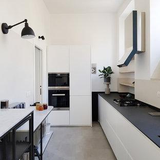 Idee per una cucina nordica chiusa con ante lisce, paraspruzzi beige, elettrodomestici neri, pavimento in cemento, pavimento grigio e top nero
