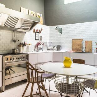 Foto di una piccola cucina design con lavello da incasso, ante lisce, ante bianche, paraspruzzi bianco, paraspruzzi con piastrelle diamantate, elettrodomestici in acciaio inossidabile, nessuna isola, pavimento con piastrelle in ceramica e pavimento bianco