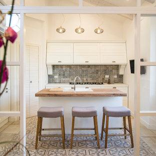 ローマの大きいシャビーシック調のおしゃれなキッチン (ダブルシンク、レイズドパネル扉のキャビネット、白いキャビネット、木材カウンター、マルチカラーのキッチンパネル、磁器タイルのキッチンパネル、白い調理設備、磁器タイルの床、マルチカラーの床、茶色いキッチンカウンター) の写真
