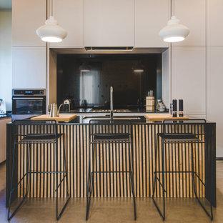 Idee per una cucina a L contemporanea con lavello sottopiano, ante lisce, ante bianche, paraspruzzi nero, paraspruzzi in lastra di pietra, elettrodomestici in acciaio inossidabile, pavimento in cemento, isola, pavimento grigio e top nero