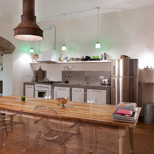 Industrial single-wall eat-in kitchen in Florence with shaker cabinets, white cabinets, concrete benchtops, medium hardwood floors and no island.