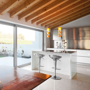 Mid-sized mediterranean l-shaped eat-in kitchen in Venice with an integrated sink, flat-panel cabinets, stainless steel benchtops, metallic splashback, metal splashback, stainless steel appliances, porcelain floors, with island and beige floor.