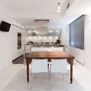 Design ideas for a large contemporary single-wall eat-in kitchen in Florence with an integrated sink, flat-panel cabinets, white cabinets, stainless steel benchtops, metallic splashback, metal splashback, stainless steel appliances, marble floors and with island.