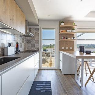 ローマの中サイズのコンテンポラリースタイルのおしゃれなキッチン (アンダーカウンターシンク、フラットパネル扉のキャビネット、白いキャビネット、木材カウンター、グレーのキッチンパネル、モザイクタイルのキッチンパネル、パネルと同色の調理設備、無垢フローリング、ベージュの床、ベージュのキッチンカウンター) の写真