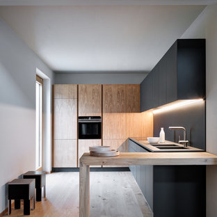 Design ideas for a modern l-shaped separate kitchen in Milan with flat-panel cabinets, black cabinets, wood benchtops, black splashback, black appliances, medium hardwood floors, brown floor, an integrated sink, no island and grey benchtop.