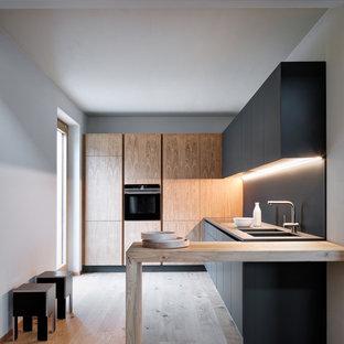 ミラノのモダンスタイルのおしゃれなキッチン (フラットパネル扉のキャビネット、黒いキャビネット、木材カウンター、黒いキッチンパネル、黒い調理設備、無垢フローリング、茶色い床、一体型シンク、アイランドなし、グレーのキッチンカウンター) の写真