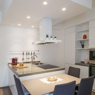 Immagine di una cucina contemporanea con ante lisce, ante bianche, penisola, lavello sottopiano, paraspruzzi bianco, elettrodomestici in acciaio inossidabile, parquet chiaro, pavimento beige e top grigio
