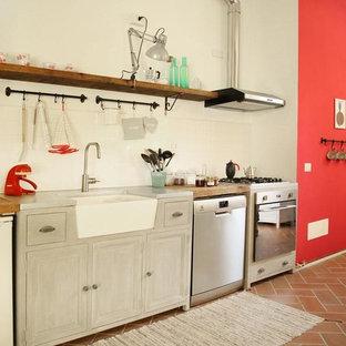 Immagine di una cucina lineare in campagna con elettrodomestici in acciaio inossidabile, lavello stile country, ante con riquadro incassato, ante grigie, top in legno, paraspruzzi bianco e pavimento marrone