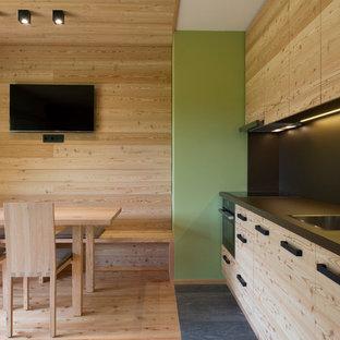 Foto di una cucina in montagna di medie dimensioni con lavello da incasso, ante lisce, ante in legno chiaro, paraspruzzi nero, elettrodomestici neri e parquet chiaro