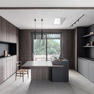 Immagine di una cucina ad U moderna con lavello da incasso, ante lisce, ante in legno bruno, isola, pavimento grigio e top grigio