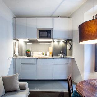 Esempio di una cucina minimal con ante lisce, ante bianche, nessuna isola, top grigio, paraspruzzi grigio e pavimento grigio