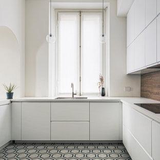 Immagine di una cucina ad U contemporanea con lavello sottopiano, ante lisce, ante bianche, pavimento in cementine, pavimento multicolore e top bianco