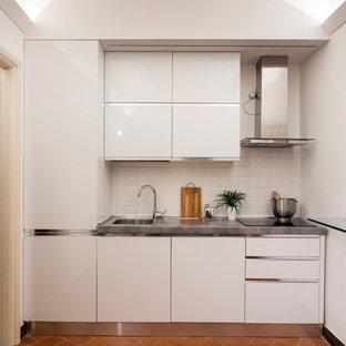 Foto di una piccola cucina lineare contemporanea con ante lisce, ante bianche, paraspruzzi bianco, nessuna isola, top grigio, lavello a vasca singola e pavimento arancione