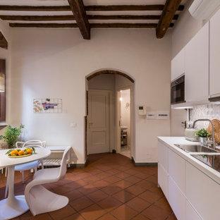 フィレンツェの中くらいの地中海スタイルのおしゃれなキッチン (ドロップインシンク、フラットパネル扉のキャビネット、白いキャビネット、マルチカラーのキッチンパネル、磁器タイルのキッチンパネル、シルバーの調理設備、テラコッタタイルの床、アイランドなし、赤い床、白いキッチンカウンター、表し梁) の写真