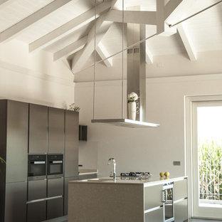 Immagine di una cucina contemporanea con lavello sottopiano, ante lisce, elettrodomestici neri, isola, pavimento grigio, ante grigie, pavimento in cemento e top beige