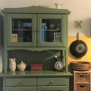 Country single-wall separate kitchen in Other with a farmhouse sink, glass-front cabinets, green cabinets, wood benchtops, yellow splashback, ceramic splashback, white appliances, porcelain floors, no island, grey floor and green benchtop.