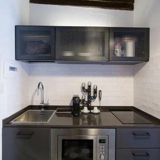 Foto på ett litet industriellt brun linjärt kök med öppen planlösning, med en enkel diskho, luckor med glaspanel, grå skåp, bänkskiva i kvarts, grått stänkskydd, stänkskydd i keramik, rostfria vitvaror, klinkergolv i porslin och grönt golv