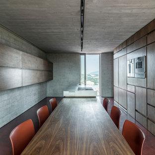 他の地域の広いコンテンポラリースタイルのおしゃれなキッチン (コンクリートの床、赤い床、中間色木目調キャビネット、ステンレスカウンター) の写真