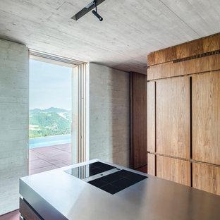 他の地域の広いコンテンポラリースタイルのおしゃれなキッチン (フラットパネル扉のキャビネット、濃色木目調キャビネット、コンクリートの床、赤い床、一体型シンク、黒い調理設備) の写真