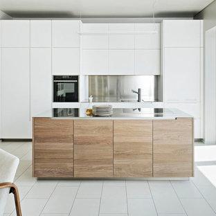 Foto di una cucina minimal di medie dimensioni con ante lisce, ante bianche, top in acciaio inossidabile, paraspruzzi a effetto metallico, elettrodomestici neri, isola e pavimento bianco