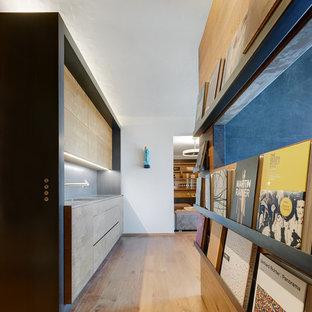 Esempio di una cucina lineare design con lavello sottopiano, ante lisce, ante in legno chiaro, paraspruzzi grigio, pavimento in legno massello medio, nessuna isola, pavimento marrone e top grigio