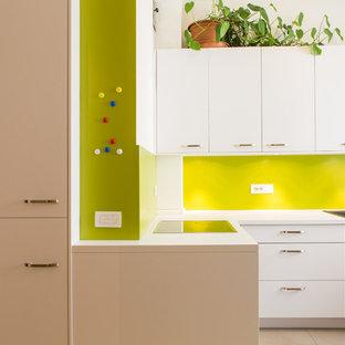 Foto di una cucina a L design con lavello a doppia vasca, ante lisce, ante bianche, paraspruzzi verde, nessuna isola, top bianco e pavimento beige