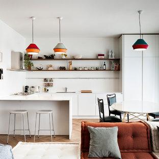 Idee per una cucina minimal con ante lisce, ante bianche, paraspruzzi bianco, pavimento in legno massello medio, top bianco, lavello sottopiano e penisola