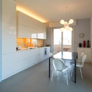 Ispirazione per una cucina minimal con lavello sottopiano, ante lisce, ante bianche, paraspruzzi arancione, paraspruzzi con lastra di vetro, elettrodomestici da incasso, pavimento in cemento, nessuna isola, pavimento grigio e top bianco