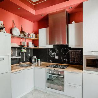 Esempio di una cucina a L design di medie dimensioni con ante lisce, ante bianche, top in legno, paraspruzzi nero, elettrodomestici bianchi, nessuna isola e pavimento bianco
