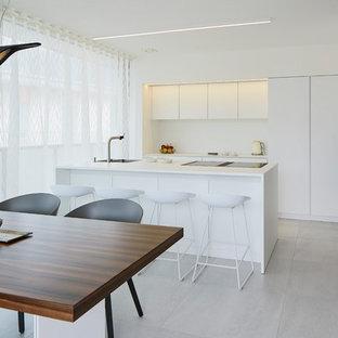 Foto di una cucina moderna di medie dimensioni con ante lisce, ante bianche, top in laminato, elettrodomestici neri, pavimento con piastrelle in ceramica, isola, pavimento grigio e paraspruzzi bianco