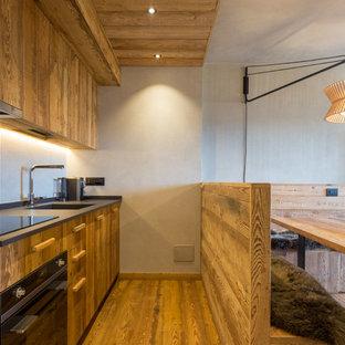 Immagine di una cucina rustica con lavello sottopiano, ante lisce, ante in legno scuro, elettrodomestici in acciaio inossidabile, pavimento in legno massello medio, nessuna isola e pavimento marrone