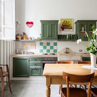 他の地域のカントリー風おしゃれなキッチン (エプロンフロントシンク、シェーカースタイル扉のキャビネット、緑のキャビネット、シルバーの調理設備の、コンクリートの床、アイランドなし、グレーの床、ベージュのキッチンカウンター) の写真