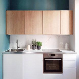 Пример оригинального дизайна: маленькая прямая кухня в современном стиле с накладной раковиной, плоскими фасадами, белыми фасадами, серым фартуком, техникой из нержавеющей стали, светлым паркетным полом, бежевым полом и белой столешницей без острова