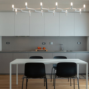 Photo of a contemporary l-shaped kitchen/diner in Turin with a built-in sink, flat-panel cabinets, grey cabinets, grey splashback, stone slab splashback, integrated appliances, light hardwood flooring, no island, beige floors and grey worktops.