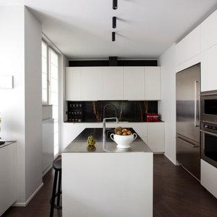 Idee per una cucina a L minimal con lavello sottopiano, ante lisce, ante bianche, paraspruzzi nero, elettrodomestici in acciaio inossidabile, parquet scuro, isola, pavimento marrone e top nero