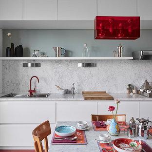 Foto di una cucina contemporanea di medie dimensioni con lavello a doppia vasca, ante lisce, ante bianche, top in marmo, paraspruzzi bianco, paraspruzzi in marmo, nessuna isola, elettrodomestici da incasso e pavimento rosso