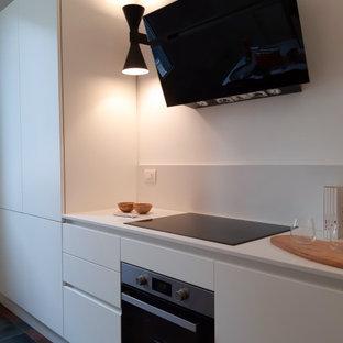 ミラノの中くらいのミッドセンチュリースタイルのおしゃれなキッチン (ドロップインシンク、フラットパネル扉のキャビネット、白いキャビネット、人工大理石カウンター、白いキッチンパネル、セラミックタイルの床、アイランドなし、赤い床、白いキッチンカウンター) の写真