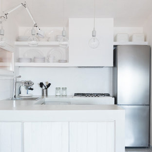 This is an example of a small transitional u-shaped open plan kitchen in Other with raised-panel cabinets, white cabinets, concrete benchtops, grey splashback, white appliances, a peninsula and a drop-in sink.