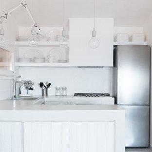 Foto di una piccola cucina tradizionale con ante con bugna sagomata, ante bianche, top in cemento, paraspruzzi grigio, elettrodomestici bianchi, penisola e lavello da incasso