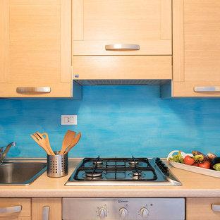 ローマの小さいビーチスタイルのおしゃれなキッチン (ダブルシンク、落し込みパネル扉のキャビネット、中間色木目調キャビネット、木材カウンター、青いキッチンパネル、セラミックタイルの床、アイランドなし、ベージュの床) の写真