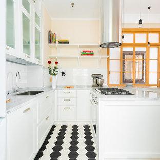 Immagine di una cucina ad U tradizionale con ante in stile shaker, ante bianche, lavello sottopiano, paraspruzzi bianco, paraspruzzi con piastrelle diamantate, penisola, pavimento nero e top grigio