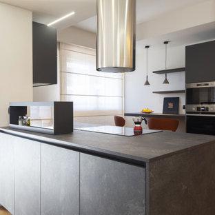 Immagine di una cucina minimal di medie dimensioni con lavello da incasso, ante lisce, ante nere, top in laminato, elettrodomestici in acciaio inossidabile, parquet chiaro, isola e top nero