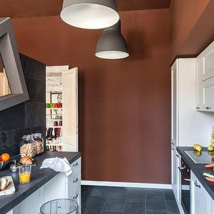 他の地域のエクレクティックスタイルのおしゃれなキッチン (一体型シンク、落し込みパネル扉のキャビネット、白いキャビネット、御影石カウンター、グレーのキッチンパネル、石スラブのキッチンパネル、シルバーの調理設備の、スレートの床、グレーのキッチンカウンター) の写真