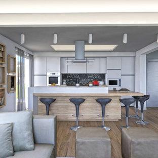 Inspiration för ett stort funkis brun brunt kök, med en nedsänkt diskho, släta luckor, vita skåp, träbänkskiva, svart stänkskydd, stänkskydd i skiffer, rostfria vitvaror, ljust trägolv, en köksö och brunt golv