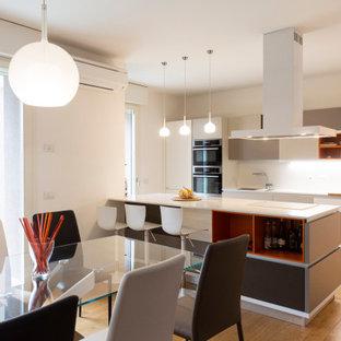 Foto di una cucina minimal di medie dimensioni con isola, lavello a vasca singola, ante lisce, ante bianche, paraspruzzi bianco, pavimento in legno massello medio, pavimento beige e top bianco