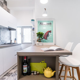 This is an example of a scandinavian galley eat-in kitchen in Milan with an undermount sink, flat-panel cabinets, white cabinets, blue splashback, panelled appliances, a peninsula, blue floor and beige benchtop.