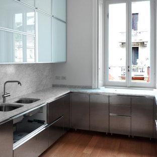 Foto di una cucina a L minimal con lavello sottopiano, ante lisce, ante in acciaio inossidabile, paraspruzzi bianco, pavimento in legno massello medio, nessuna isola, pavimento marrone e top bianco