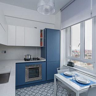 Esempio di una cucina a L contemporanea chiusa e di medie dimensioni con lavello sottopiano, ante lisce, ante blu, paraspruzzi grigio, elettrodomestici in acciaio inossidabile, nessuna isola e pavimento blu